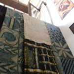 """A collection of Yoruba hand woven and hand printed textiles at the African Heritage House. These textiles will be exhibited at the French Cultural Centre from 9-29 October. At the left is a piece of """"Aseoke"""", woven by men on narrow hand looms. The other cloths are examples of """"Adire"""" with designs painted with cassava starch using a palm frond or feather, The cloth is then dipped several times in blue=black indigo dye,. Then the starch is chipped off and the cloth is dipped once more to get the light blue colour. copyright Rupi Mangat"""