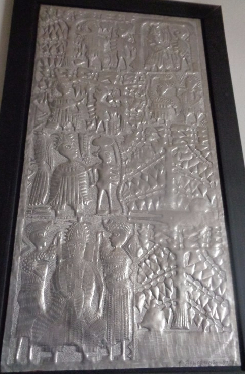 """Hammered aluminum panel by the late Asiru Olatunde from Oshogbo Nigeria. Asiru was a former blacksmith who started rolling out metal panels depicting Yoruba mythology in the 1960s. His son Folorunso is carrying on this craft. This panel depicts the """"Story of the Four Breasted Woman"""""""