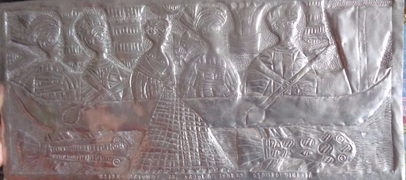 This is one of the metal panels based on Yoruba legend and mythology created by the late Asiru Olatunde and his son Folorunsho. This panel depicts women feeding the fish in the sacred river Osun, where women from all over the world come seeking fertility.