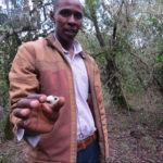 Njogu with the now rare snail at the Mount Kenya Resource Centre nature trail - copyright Rupi Mangat